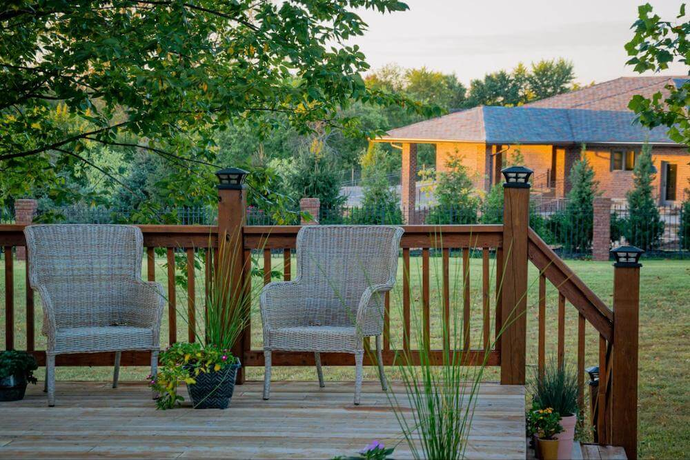 backyard porch with two porch chairs looking out over a large lawn